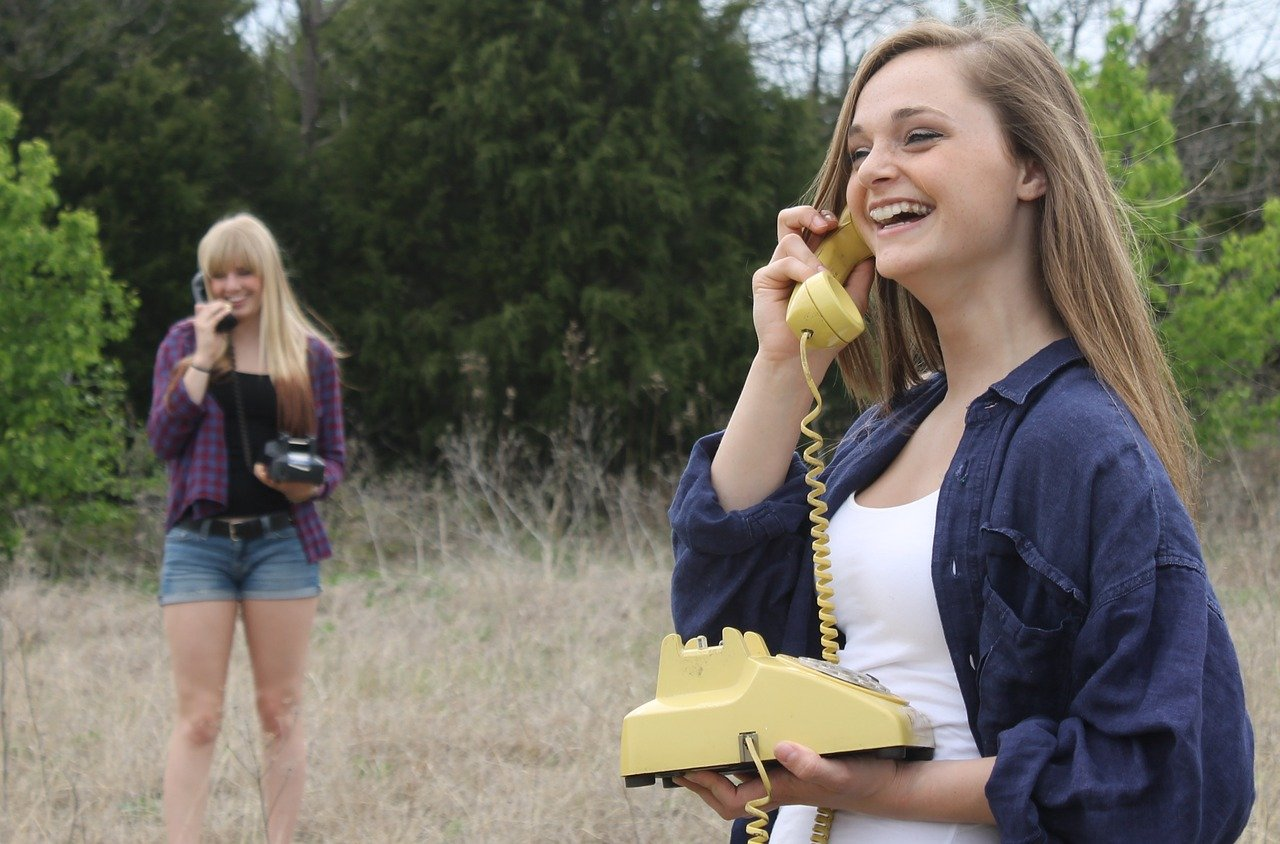 two young women talking on the phone