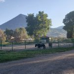 farm with horse arena and mountains