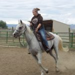 woman riding a horse as part of equine therapy